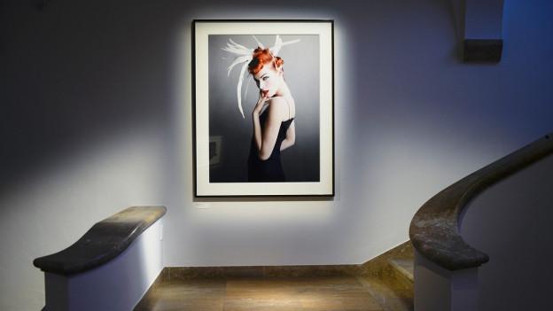 Ein Treppenaufgang, an der Wand das Bild einer Frau mit Hochsteckfrisur.
