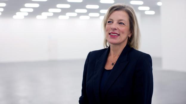 Eine Frau steht in einem Ausstellungsraum.