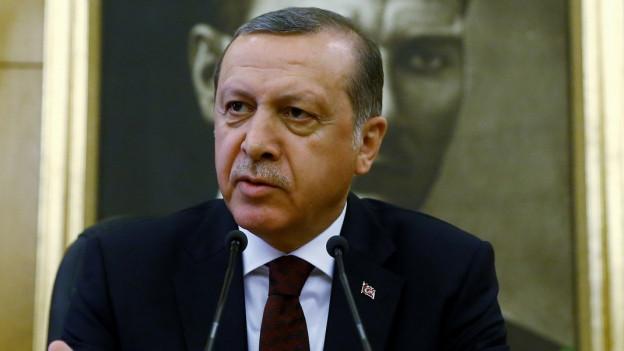 Ein türkischer Mann im Anzug spricht in ein Mikrofon.