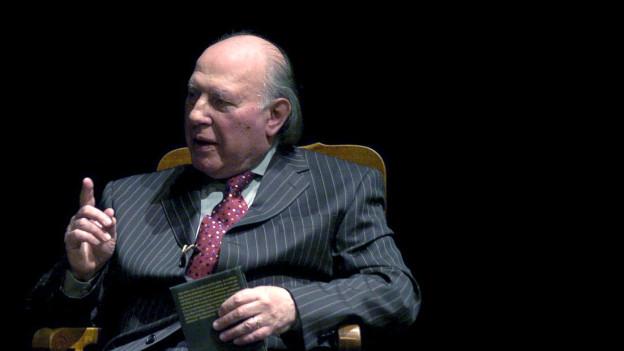 Ein älterer Herr im Anzug spricht und erhebt seinen Zeigefinger mahnend.