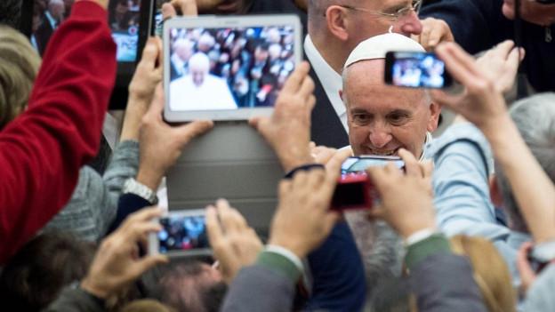 Der Papst, umringt von Menschen und Mobiltelefonen.