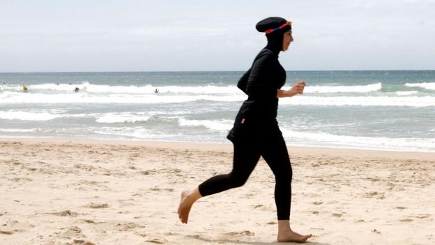 Eine Frau in einem Burkini rennt am Strand