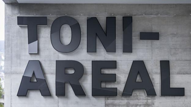 """Schriftzug """"Toni Areal"""" auf einer grauen Hauswand."""