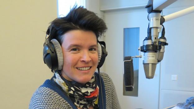 Eine Frau mit kurzem schwarzem Haar steht im Radiostudio und trägt Kopfhörer.