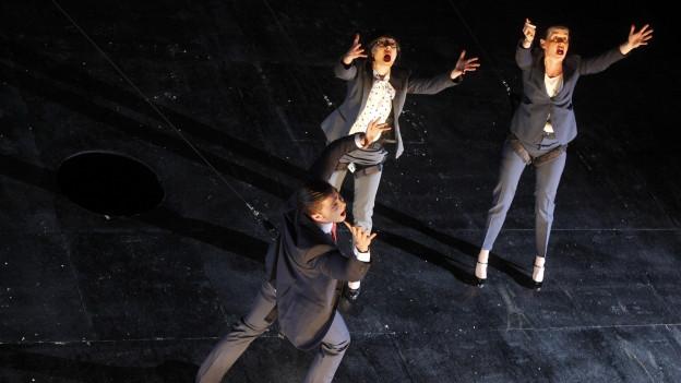 Zwei frauen und ein Mann stehen auf der Bühne und haben ihre arme nach oben gestreckt.