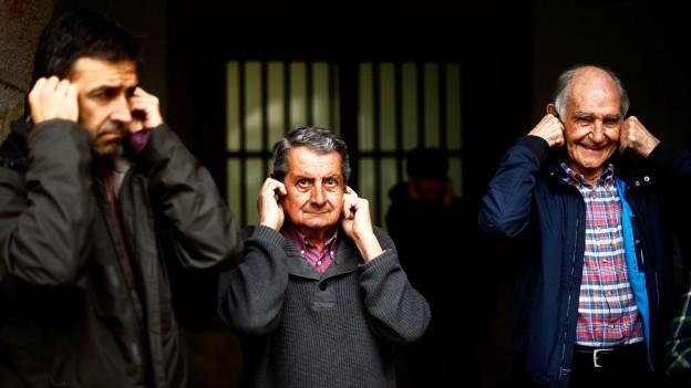Drei Männer halten sich die Ohren zu.