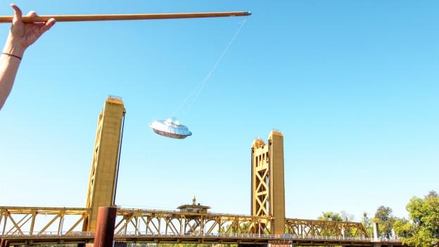 Eine Person hält eine Rute, an der ein selbstgebasteltes UFO hängt
