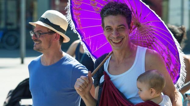 Zwei Männer, der eine trägt ein Baby auf dem Arm, an einer Demonstration für den Vaterschaftsurlaub.