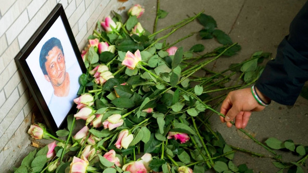 Eine Person legt eine Rose zum Bild von Suleyman Taskopru, der im Jahre 2001 vom NSU ermordet wurde.
