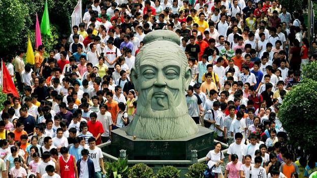 Symbolbild: Chinesische Studenten laufen an einer riesigen Konfuzius-Büste vorbei.