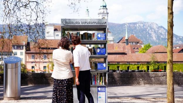 Strassenszene in Solothurn: Zwei Passanten stehen vor einem Bücherschrank an den 38. Solothurner Literaturtagen.