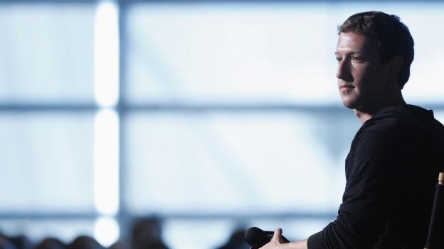 Marc Zuckerberg (blonde Kurzhaarfrisur) steht vor blauem Hintergrund.