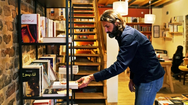 Ein Mann räumt ein Buch in einer Buchhandlung in ein Regal.