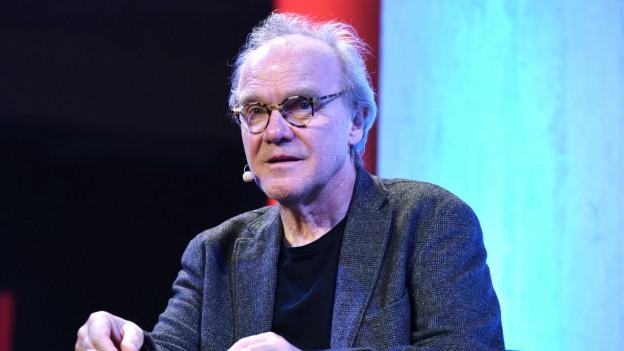 Ein Mann mit Hornbrille referiert an einem Tisch sitzend.