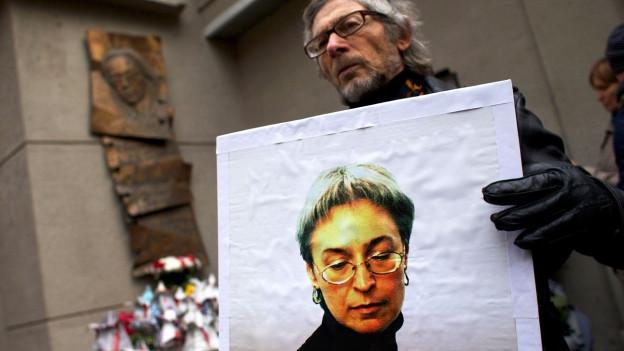 Ein Mann hält ein Bild der ermordeten Journalistin Anna Politkovskaja in die Luft.