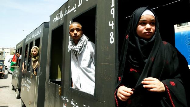 Ein Zug mit offenen Fenstern, aus denen Männer und Frauen (mit Kopftüchern) schauen.