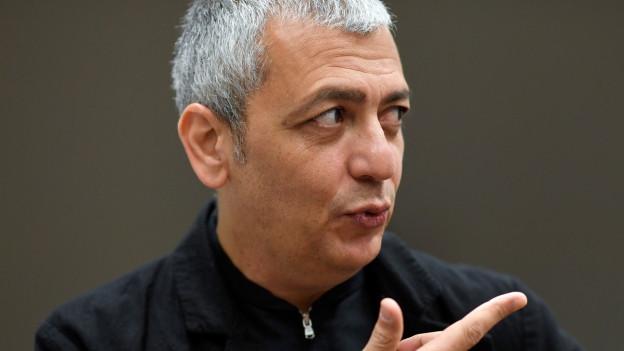 Ein Mann im schwarzen Hemd.