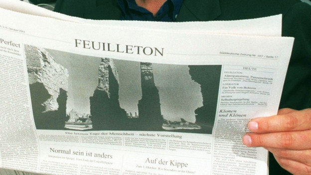 Symbolbild: Eine Person liest den Feuilleton Teil einer Sendung