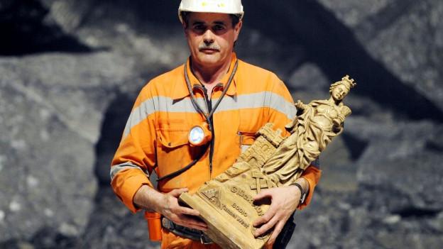 Ein Arbeiter des Gotthardbasistunnel hält eine Statue der heiligen Barbara.