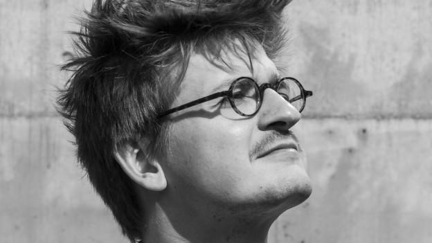 Schwarzweissfoto: ein junger Mann mit Strubelhaar und runder Brille.