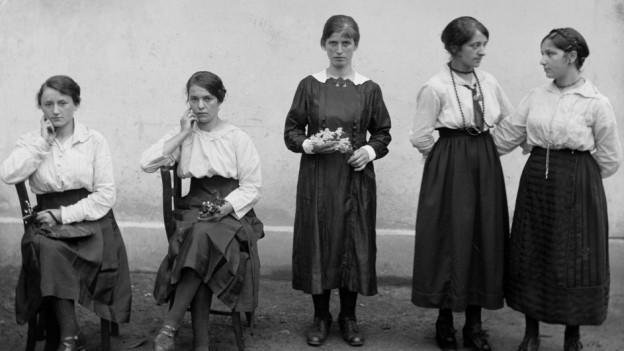 Fünf Frauen mit weissen Blusen und schwarzen Röcken.