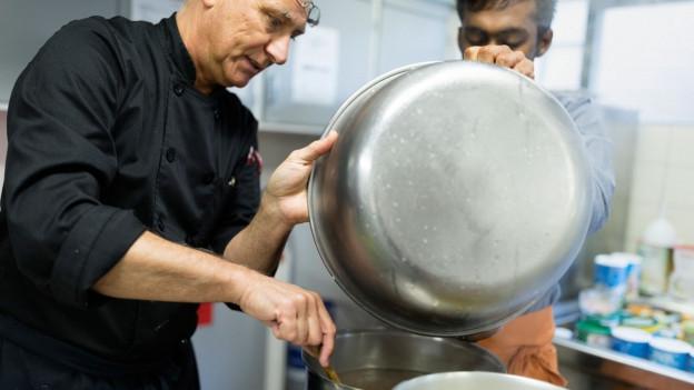 Symbolbild: Eine Betreuungsperson und ein Mann im Asylverfahren kochen gemeinsam.