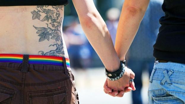 Nahaufnahmen von zwei Personen, die sich an den Händen halten.