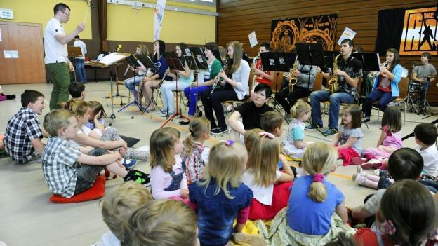 Ein Jugendorchester spielt vor einer Gruppe Kinder.