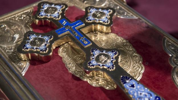 Prachtvolles Silberkreuz auf rotem Grund.