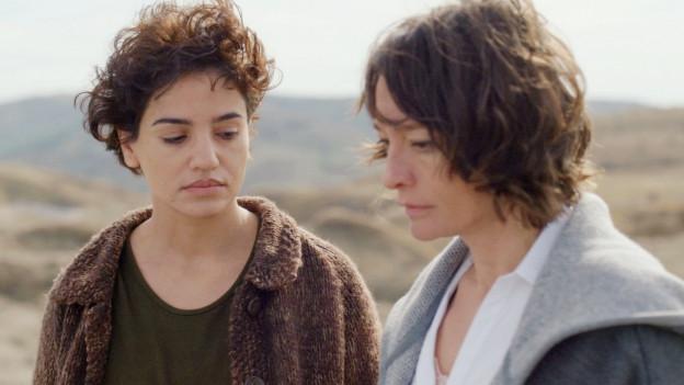 Zwei Frauen reden zusammen am Strand.