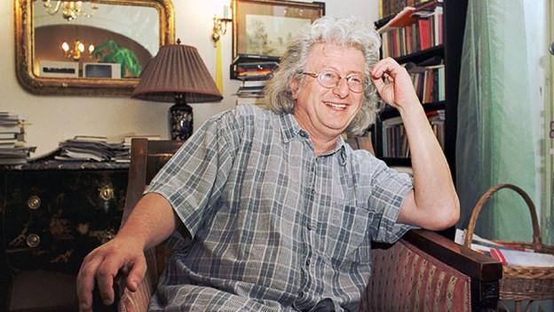 Peter Esterhazy sitzt in einem Sessel und lacht.