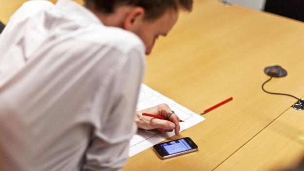 Ein Mann liest etwas auf seinem Smartphone.