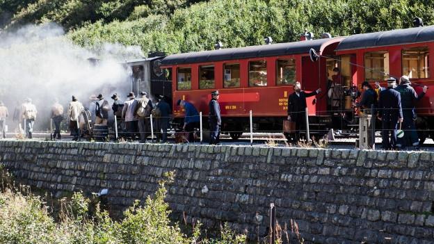 Dampflokomotive mit einsteigenden Passagieren. Ganz rechts sieht man das Filmteam.