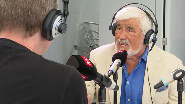 Mario Adorf sitzt mit Kopfhörern vor einem Mikrofon