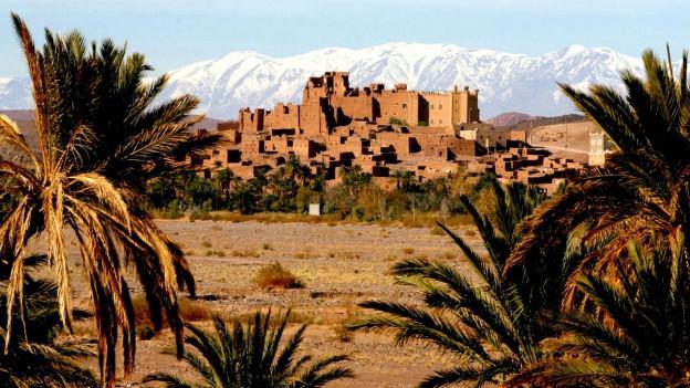 Symbolbild: Eine Kasbah in Marokko, im Hintergrund ist das Atlasgebirge zu erkennen.