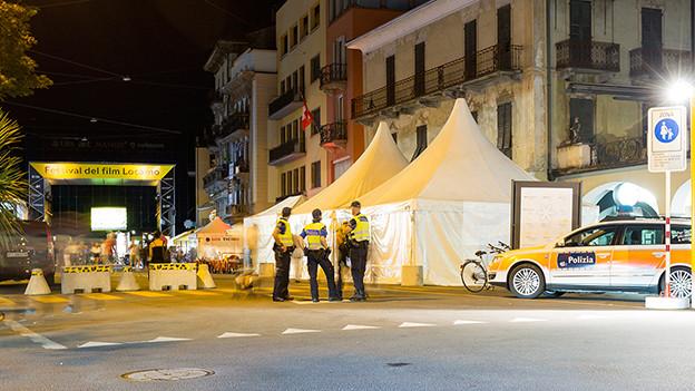 Zwei Polizisten stehen neben einem Polizeiauto vor dem Eingang zur Piazza Grande.