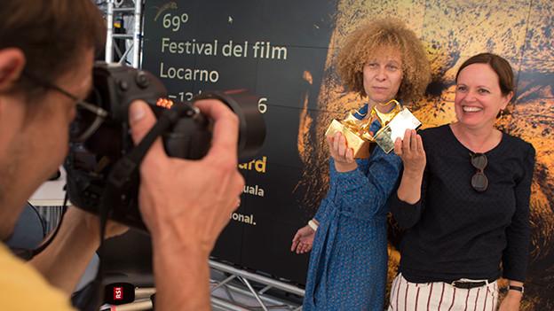 Zwei Frauen posieren mit eiener goldenen Leopardenstatue für einen Fotografen.