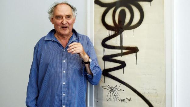 Der graffiti Künstler Harald Naegeli vor einem seiner Werke.