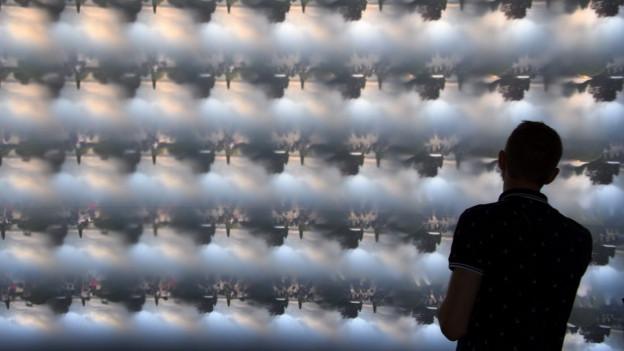 Ein Mann an der Museumsnacht vor einem beleuchteten Display.