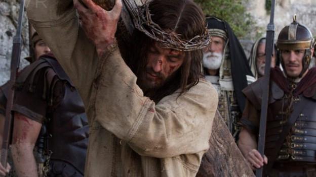 Jesusdarsteller mit Kreuz auf dem Rücken.