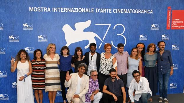 Viele Personen stehen vor einem Werbetransparent der Biennale.