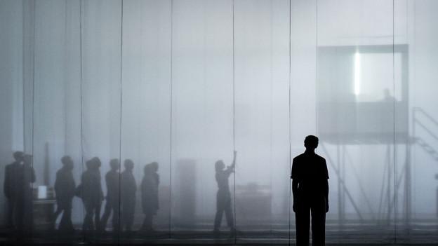 Bühnenbild: Menschen im Nebel.