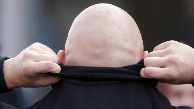 Ein Glatzkopf von hinten, zur Hälfte in einem schwarzen Pullover verborgen,R