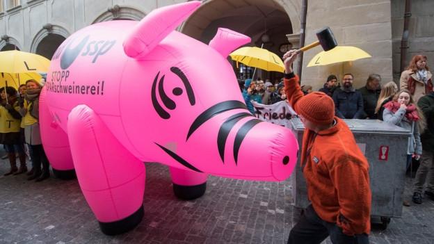 Menschen demonstrieren auf der Strasse mit einem grossen aufgeblasenen Sparschwein.