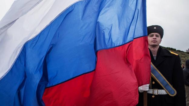 Flagge Russlands, daneben ein Soldat.