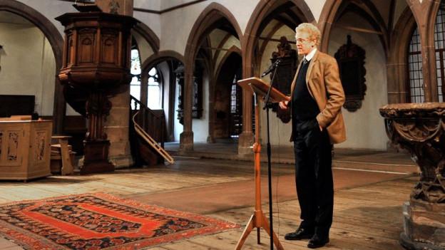 Niklaus Peter steht in einer Kirche und redet vor einem Mikrofon.