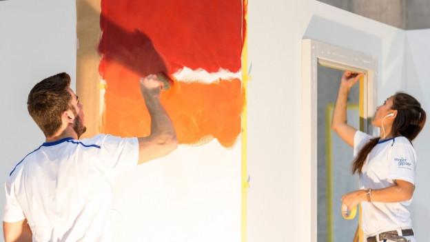 Eine Malerin und ein Maler bei der Arbeit.