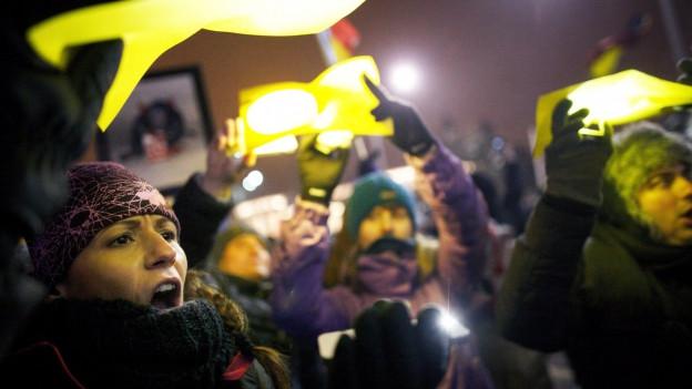 Protestierende halten buntes Papier hoch.
