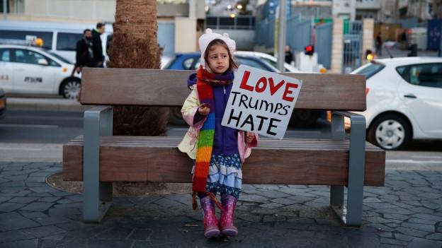 Mädchen hält ein Plakat, auf diesem steht: «Love Trumps Hate»