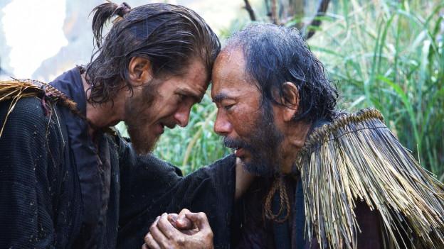 Bildausschnitt aus dem Film: Zwei Männer halten sich gegenseitig die Hände. Ihre Köpfe berühren sich.